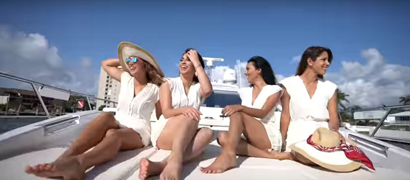 group of women sitting on the bow of an azimut