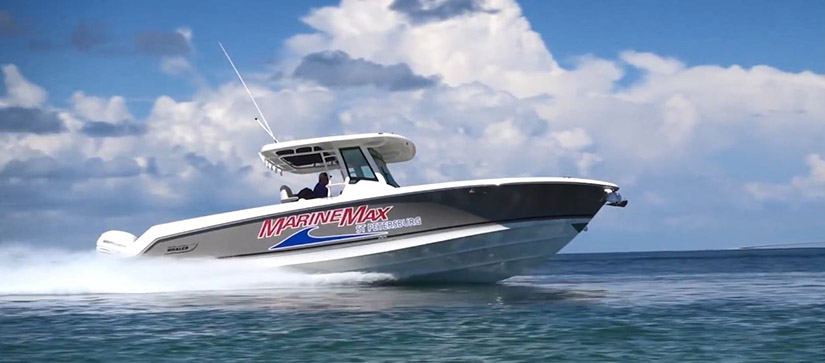 A MarineMax Boston Whaler cruises through the water from left to right.