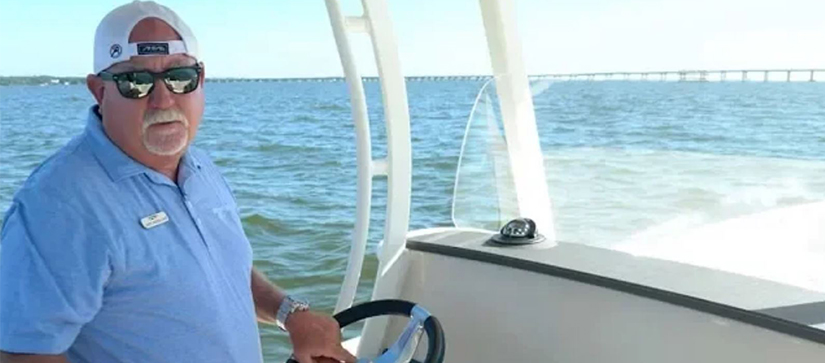 man wearing backwards hat at the helm of a boat