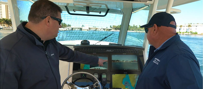 Two men pointing at a boat navigation screen