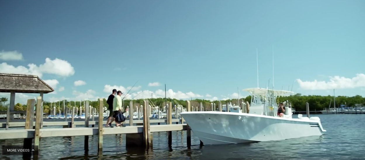 Two men walking along a dock towards their yacht with fishing gear