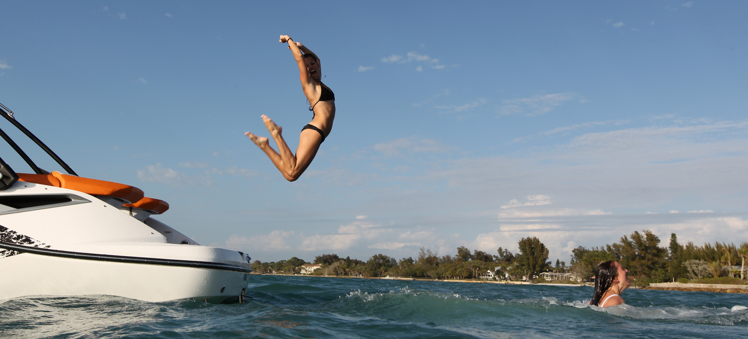Women excitedly jump off a yacht into the blue water