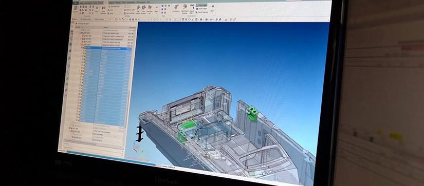 A computer screen shows a boat design