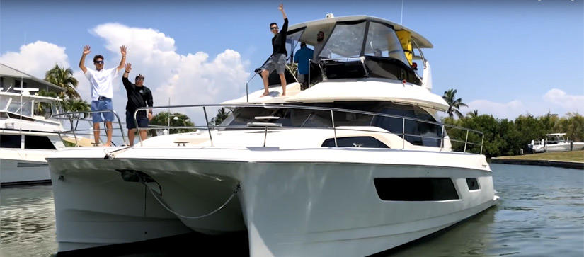Aquila team standing on bow and flybridge of Aquila  Power Catamaran with hands raised in excitement.