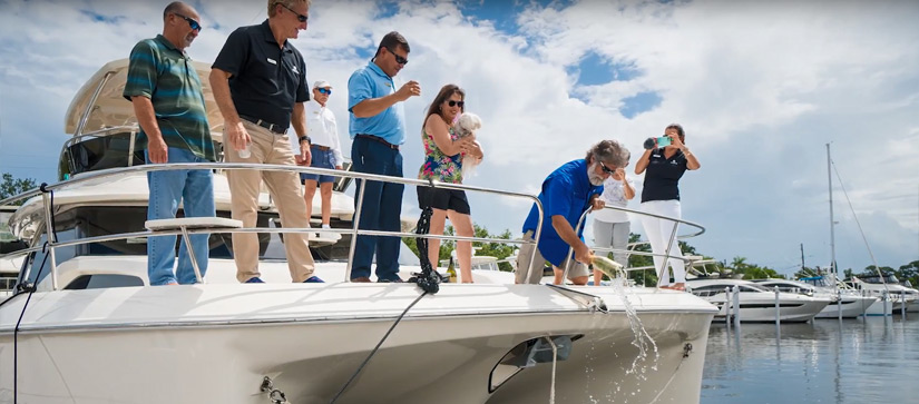 Group of boaters on bow of Aquila power catamaran for christening and one is breaking champagne bottle on anchor.