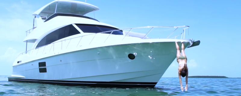 woman diving into the water from a Hatteras 60 Motor Yacht