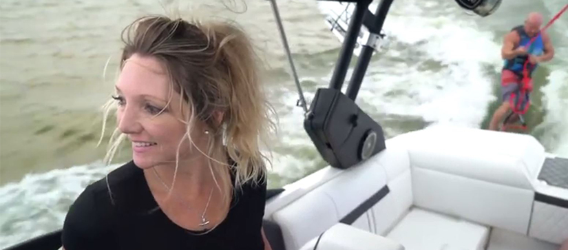woman driving boat and man wake-boarding behind it