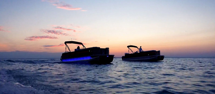 two pontoons on the water at sunset