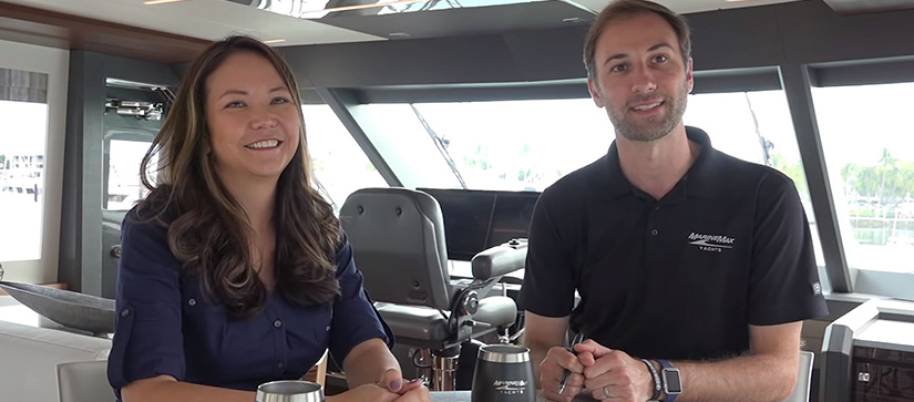 A man and woman smiling while on an Ocean Alexander yacht