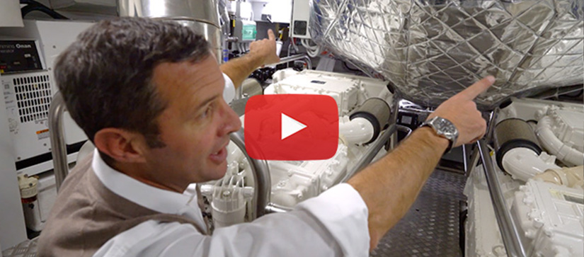 A man pointing at a machine inside an Azimut Grande 25 Metri engine room