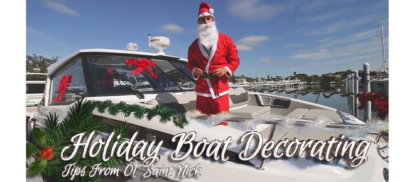 A man in a Santa Claus costume standing aboard a decorated boat