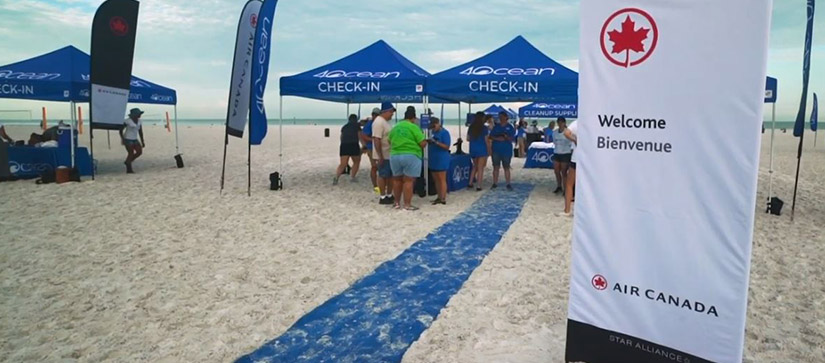 A blue carpet on a beach leading to a blue tent with 4ocean's logo on it, and people standing at a table underneath