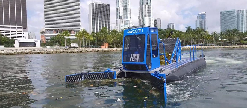 A blue vessel with the 4ocean logo on it, cruising the water and skimming up trash on the surface