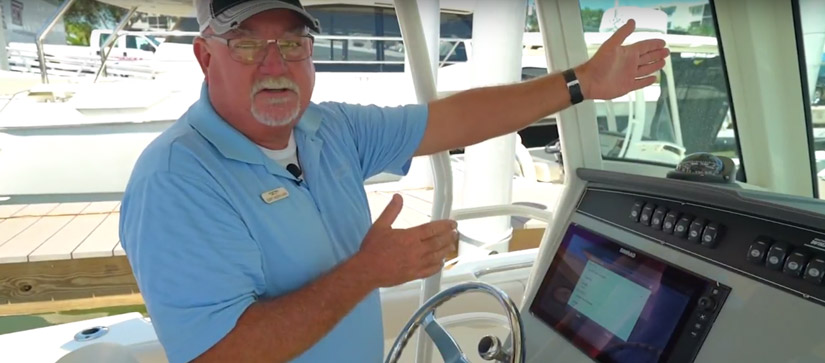 Man by the helm of a boat talking - Boating Tips Video on Simrad Chartplotters