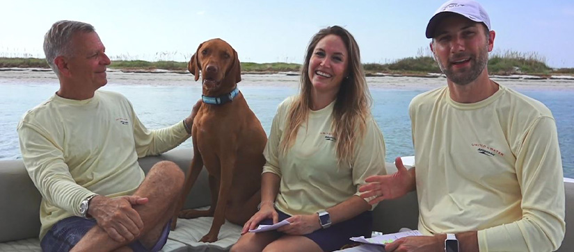 Two men and a woman on a boat with a brown dog, smiling at the camera and talking about #MMXPets