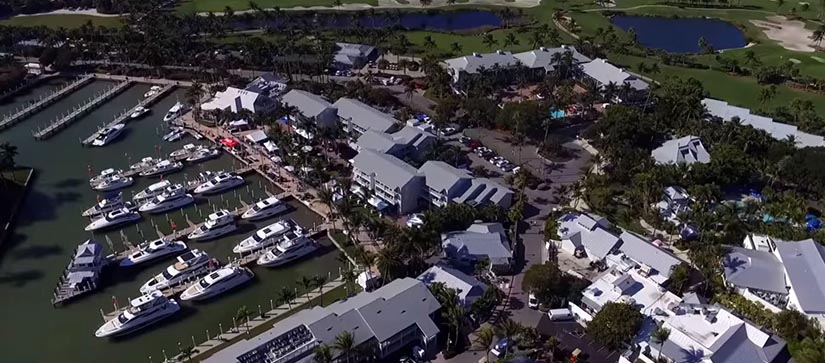 overhead the South Seas Island Resort with several yachts in the water tied to the dock, buildings, and golf course.