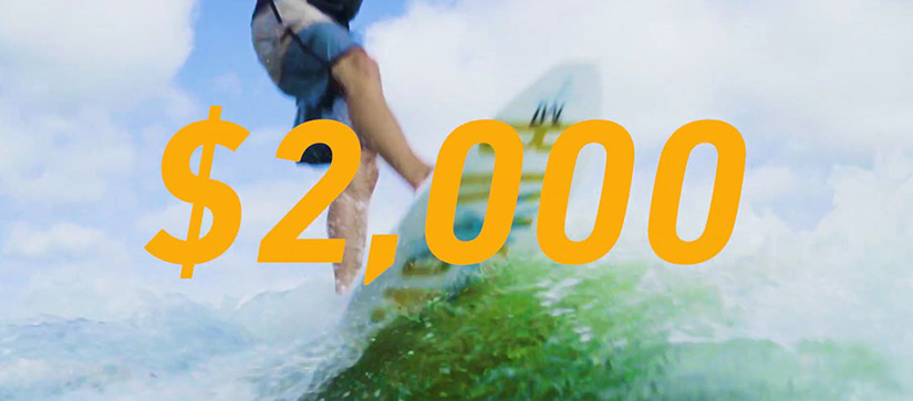 """A graphic saying """"$2,000"""" with a surfer in the background"""