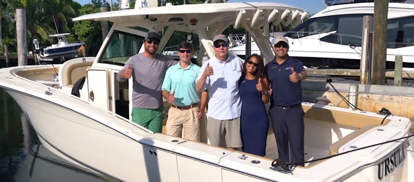 Customers and MarineMax Miami team on new boat smiling