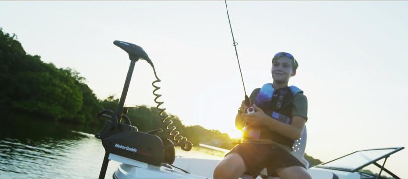 Boy sitting on a yacht fishing at sunset