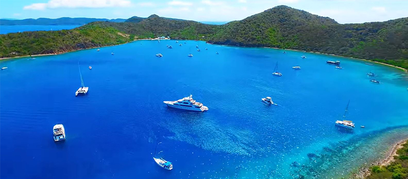large blue body of water surrounded by green islands with hills and boats anchored in the water