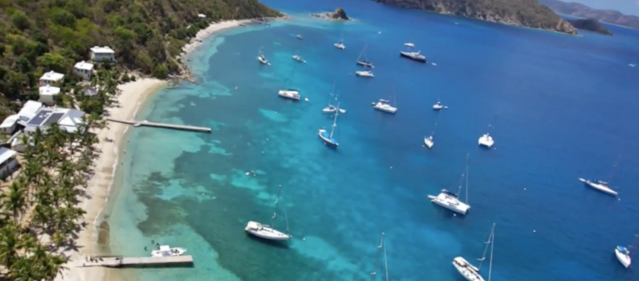 aerial view of crystal clear blue ocean speckled with white yachts