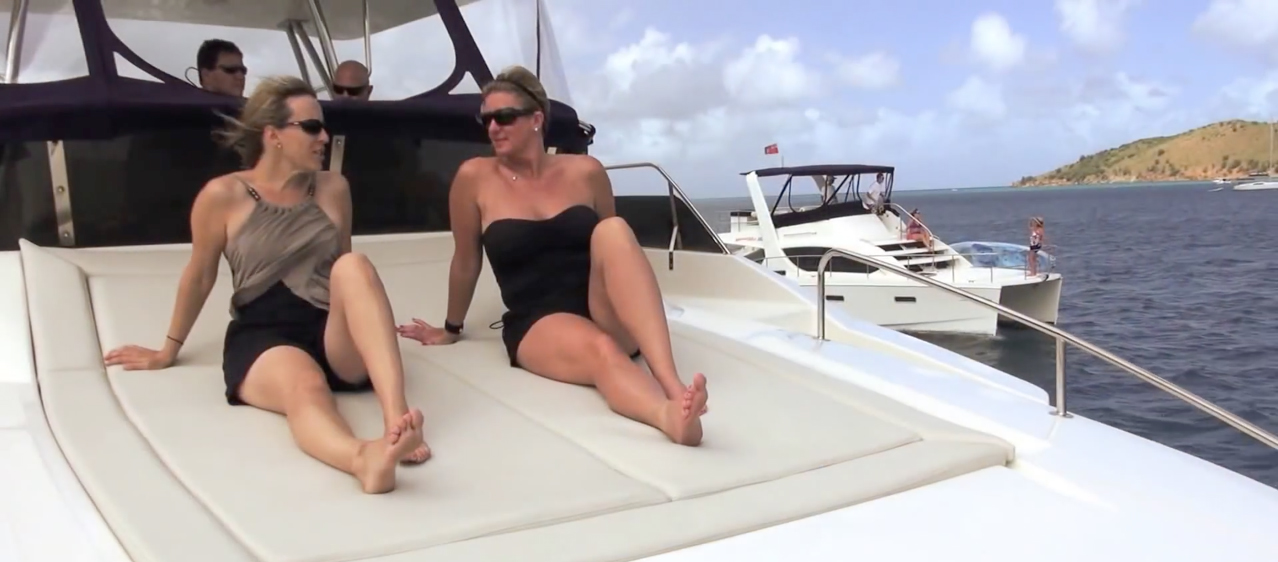 two women at front of boat sunbathing and enjoying casual conversation