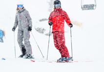 two skiers standing together while it is snowy