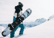 a person walking uphill in the snow while holding a burton snowboard and wearing snow sports clothing