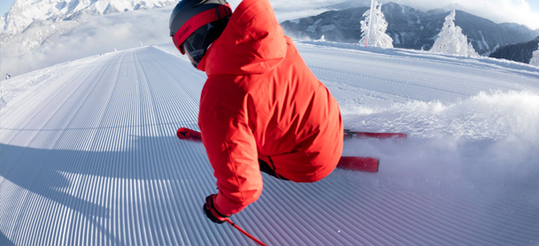 a skier wearing a red ski jacket and a black helmet skiing down freshly groomed slopes
