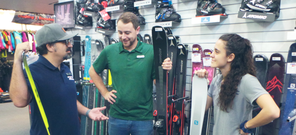 three snow ski experts discussing the features of new snow ski products in front of a snow ski display