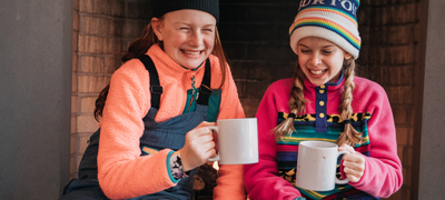 wo young girls wearing cozy winter clothing with warm drinks in mugs
