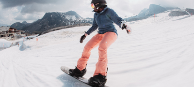 young woman snowboarding on a wide ski slope with mountains in the background