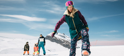 a women stepping into her snowboard bindings with her family in the background