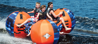 three kids having fun on an inflatable being towed through the water
