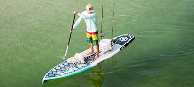man paddling while standing on a stand up paddle board with two fishing poles resting on the back