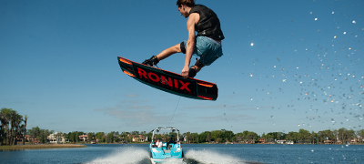 woman-catching big air on a red and balck ronix wakeboard behind a reef blue Nautique Super Air 230