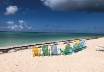 view of a beach in british virgin islands with colorful adirondack chairs