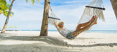 Person in hammock between palm trees on the beach