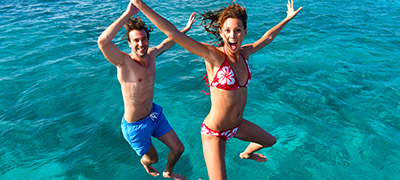 Couple jumping into water with excited faces