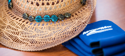 Hat on table with MarineMax Vacations Koozies