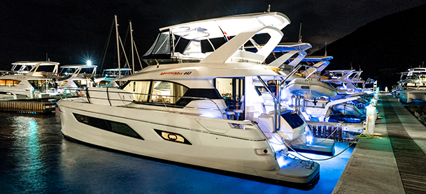 Power catamarans lit up at night on dock