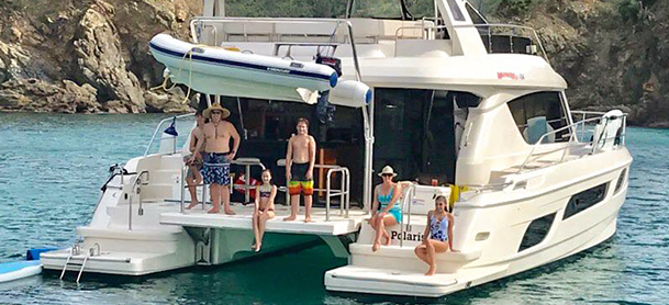 People on back of power catamaran