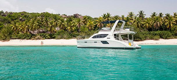 An Aquila power catamaran close to the shore of a beach