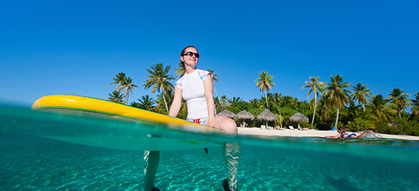 A woman sitting on a yellow surfboard in the water