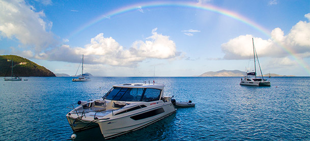An Aquila power catamaran in the water under a rainbow in the sky