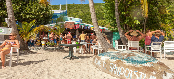 A beach bar in the British Virgin Islands with people in bathing suits standing and holding drinks