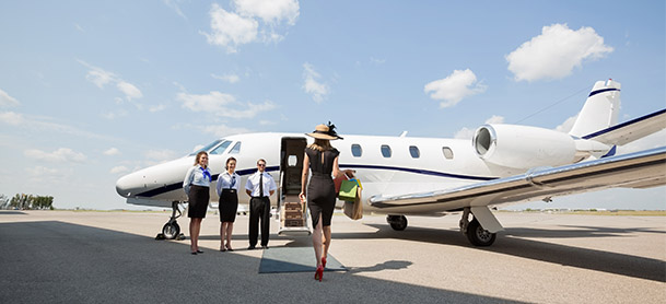 Woman walking towards a private jet and jet crew is standing outside.
