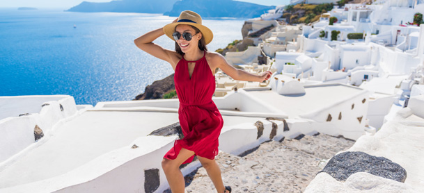 Woman in red dress and hat running through Greece