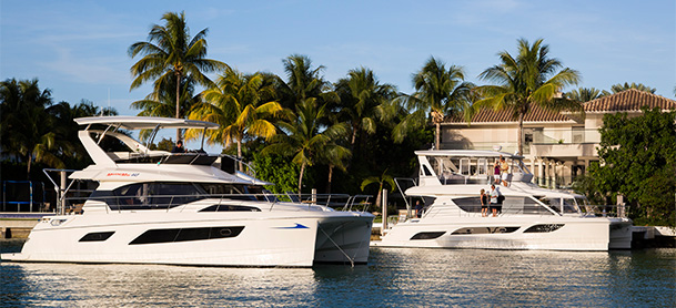 MarineMax 443 and 484 power catamarans in water next to house
