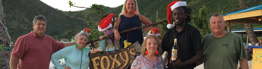 Group of friends standing with the Foxy's sign and wearing Santa hats